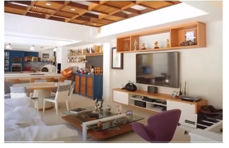 O cômodo é integrado à sala, que tem home theater e decoração em madeira e cores Reprodução