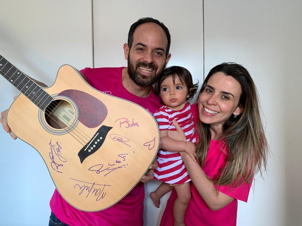 Kyara, a bebê do DF que precisa do remédio considerado o mais caro do mundo, ganhou violão autografado pelo Jota Quest para rifa online — Foto: Arquivo pessoal