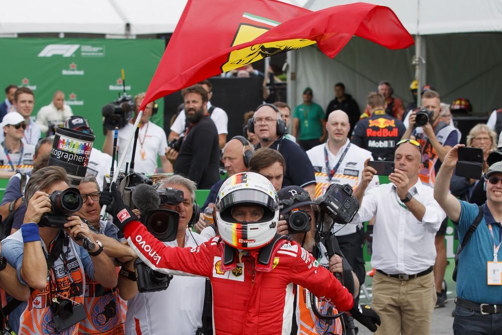 Vettel agita bandeira da Ferrari na volta aos boxes no Canadá (Foto: Reuters)