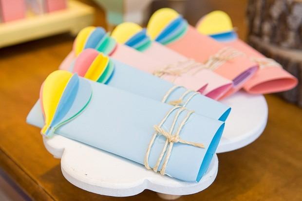 Barras de chocolates foram embrulhadas com papel colorido e receberam um acabamento com barbante e um balão em 3D. Repare que elas estão posicionadas em uma bandeja em formato de nuvem  (Foto: Danilo Giunchetti)