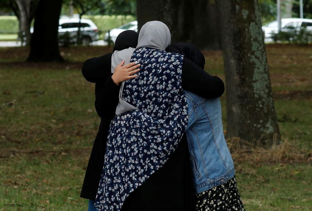 Pessoas se abraçam perto de mesquita na Nova Zelândia neste domingo (17) — Foto: Jorge Silva/Reuters