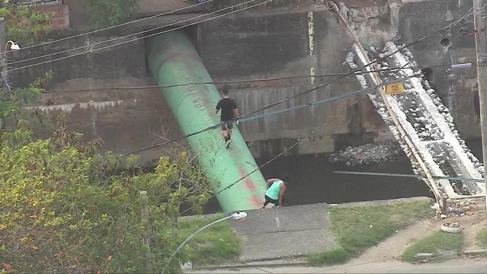 Moradores utilizam tubulação como ponte após destruição da estrutura  — Foto: Reprodução/TV Globo