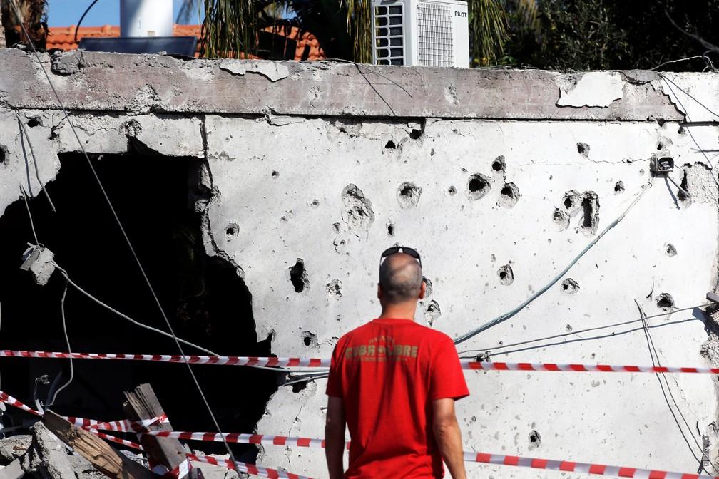 Homem olha nesta terça-feira (13) prédio danificado na cidade israelense de Ashkelon. Ele foi atingido por míssil lançado a partir da Faixa de Gaza  — Foto: Ronen Zvulun/ Reuters