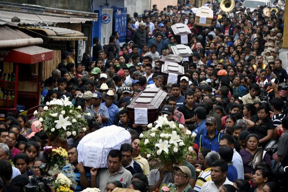 Corpos de vítimas da erupção do Vulcão de Fogo, na Guatemala, são carregados por multidão pelas ruas de Alotenango, em  Sacatepequez (Foto: Johan Ordonez / AFP)