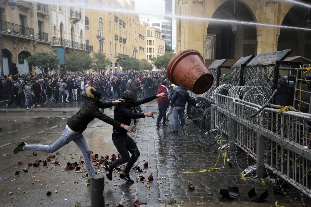 Manifestante joga um vaso em bloqueio policial perto do Parlamento do Líbano, em Beirute, neste sábado (18) — Foto: Hassan Ammar/AP Photo