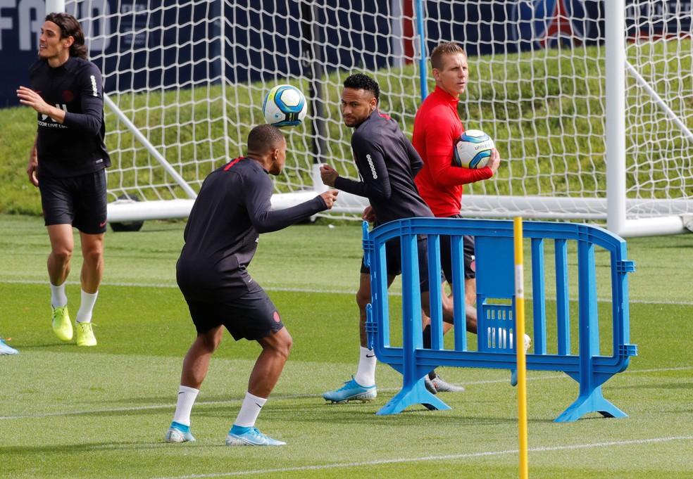 Cavani, ao fundo, Mbappé, cabeceando, e Neymar no treino do PSG — Foto: REUTERS/Philippe Wojazer