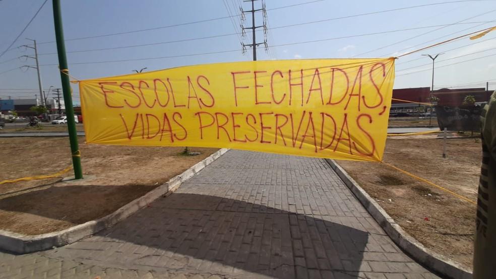 """Além das cruzes, uma placa com a frase """"escola fechada, vidas preservadas"""" foi estendida no local. — Foto: Eliana Nascimento/G1 AM"""