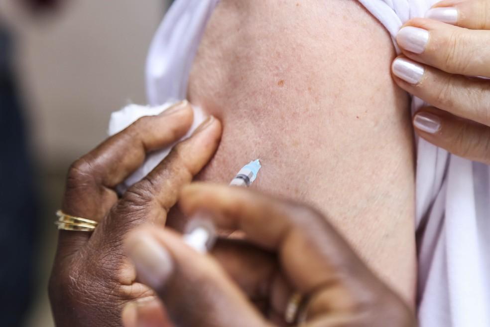 Enfermeira aplica vacina no braço de mulher (Foto: Prefeitura de Curitiba/Divulgação)