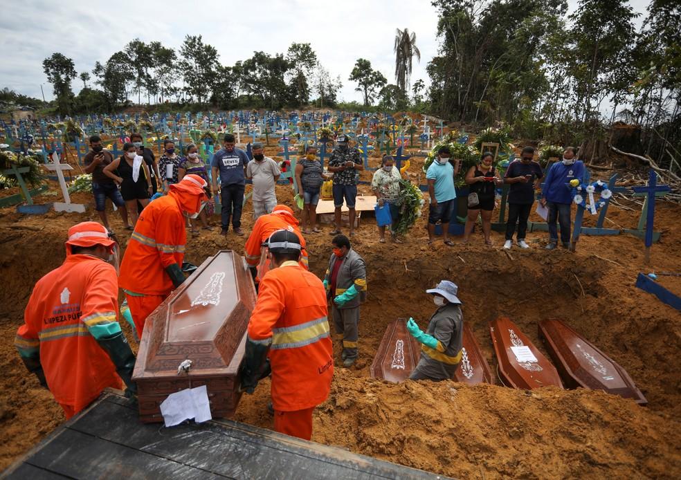 Coveiros colocam caixões de vítimas do novo coronavírus em vala comum no cemitério Parque Taruma, em Manaus. As mortes mais que dobraram na cidade desde o início da pandemia — Foto: Bruno Kelly/Reuters