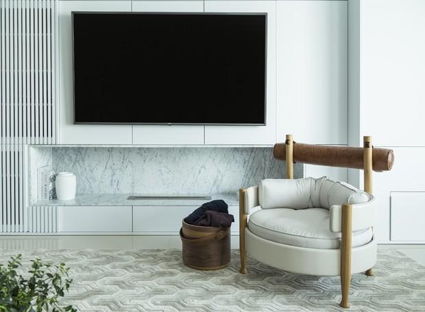 A lareira fica embutida no nicho de mármore carrara - uma proteção térmica especial impede que o calor alcance a TV (Foto: Mariana Boro/Divulgação)