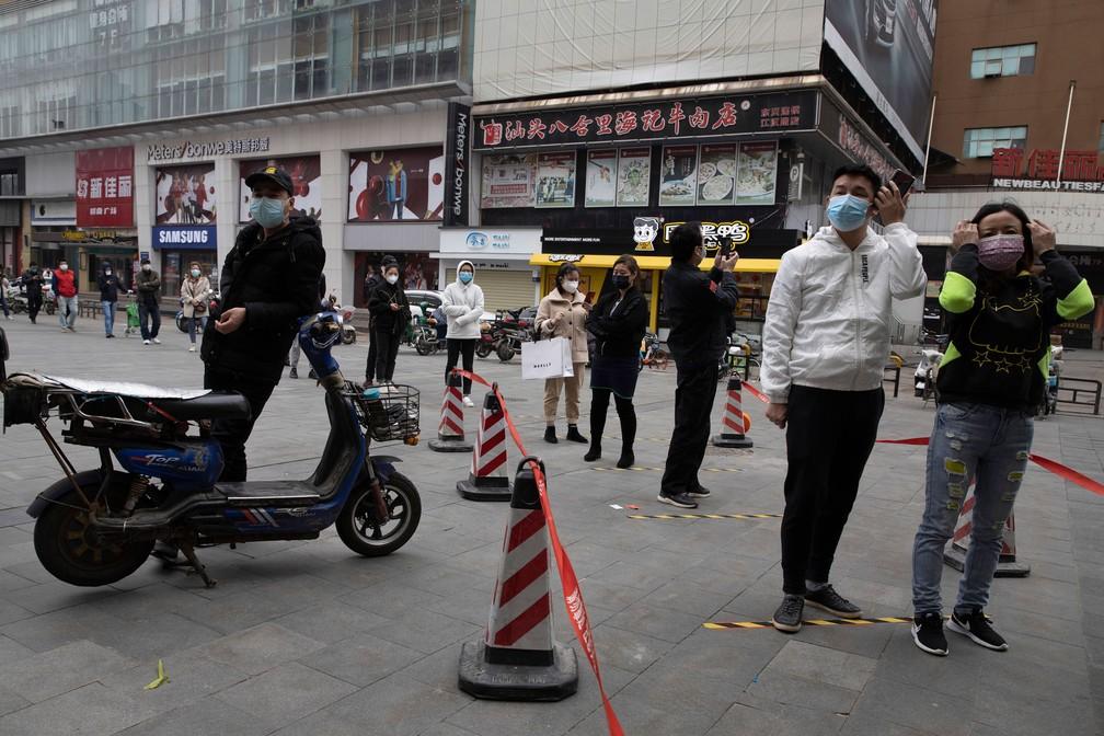 3 de abril - Moradores de Wuhan, epicentro da pandemia de Covid-19, usam máscaras para ir ao supermercado nesta sexta-feira (3)  — Foto: Han Han Guan/AP