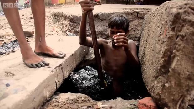 Indiano entra em bueiro para fazer limpeza de fossa (Foto: BBC News)
