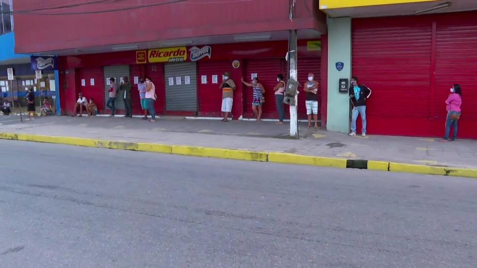 Beneficiários aguardam em fila abertura da agência da Caixa, em São Lourenço da Mata, nesta terça-feira (26) — Foto: TV Globo/Reprodução