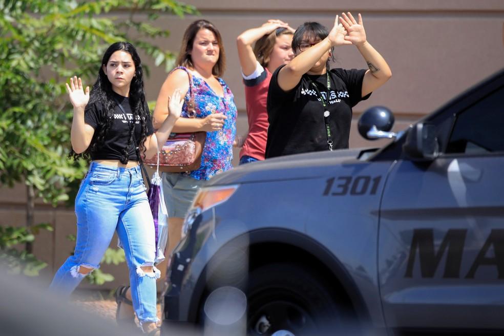 Frequentadores do centro comercial saem com as mãos ao alto depois de um tiroteio em El Paso, no Texas, neste sábado (3). — Foto: Jorge Salgado/Reuters