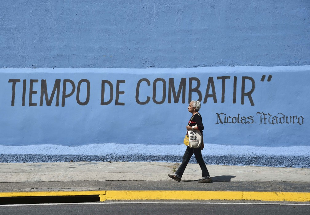 Mulher caminha ao lado de muro com a inscrição 'Tempo de Combater', que é atribuída ao presidente venezuelano, Nicolás Maduro — Foto: Yuri Cortez / AFP