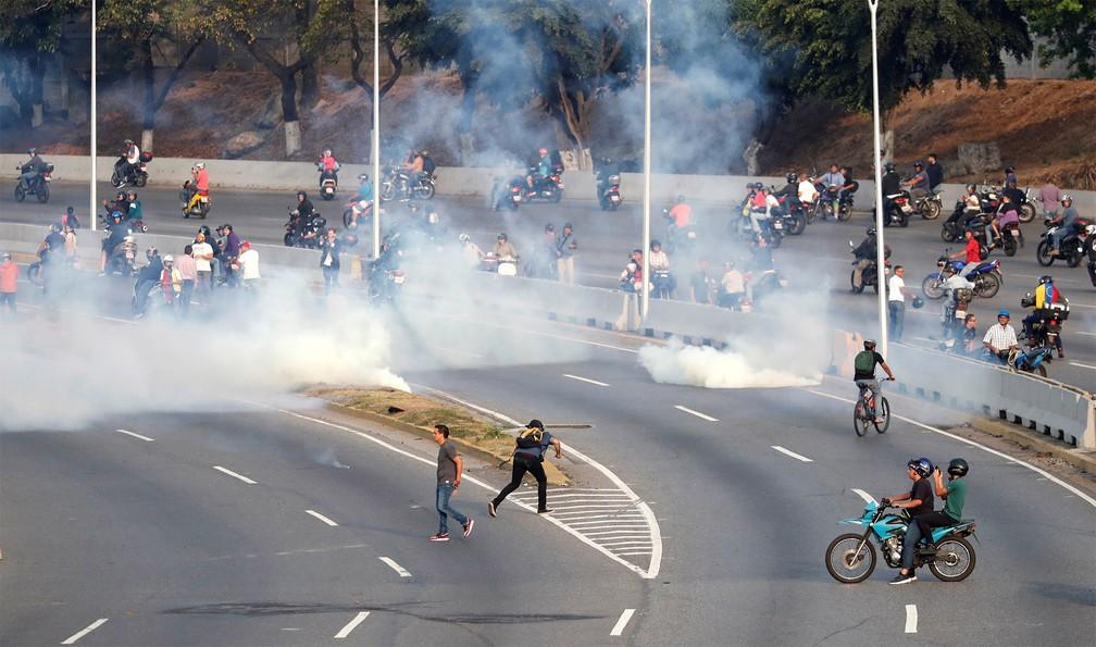 Pessoas reagem a bombas de gás lacrimogêneo atiradas perto da Base Aérea 'La Carlota' Generalísimo Francisco de Miranda, em Caracas, na Venezuela — Foto: Carlos Garcia Rawlins/Reuters