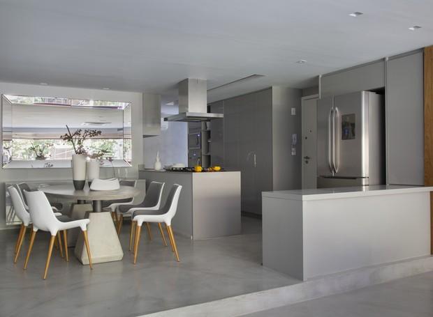 Livre de paredes, a cozinha aparece ao lado da sala de jantar, do estar e da varanda (Foto: Denilson Machado/ MCA Estúdio/Divulgação)