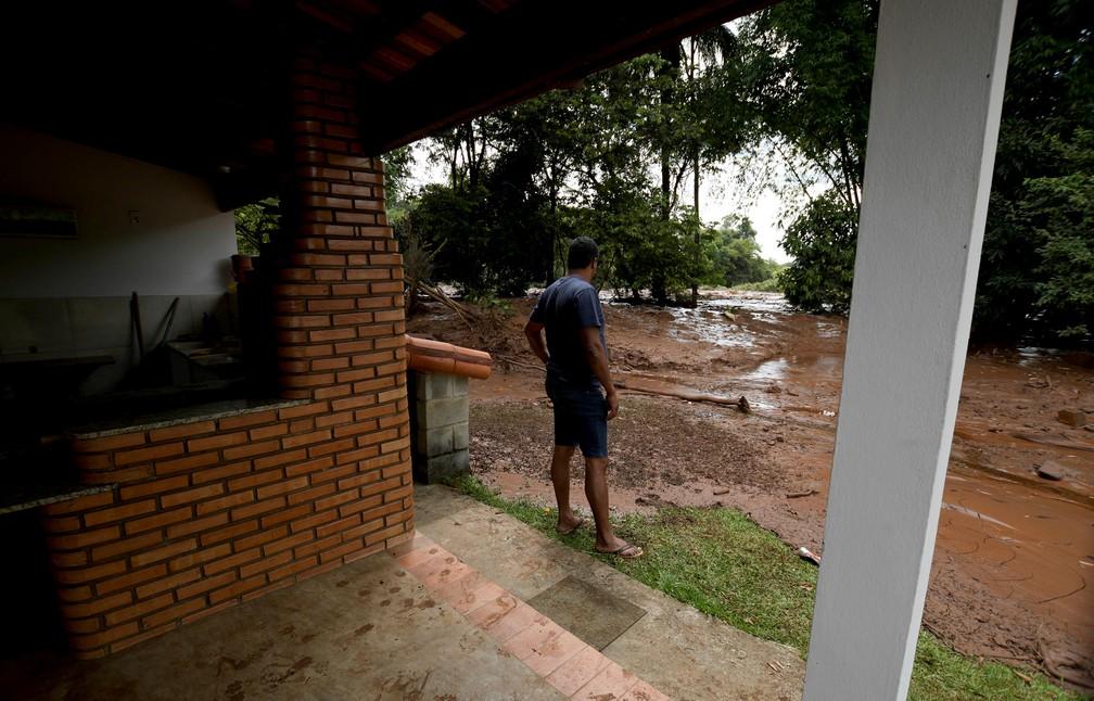 Morador observa a lama passando por sua casa em Brumadinho neste sábado (26), após o rompimento da barragem da Vale. — Foto: Washington Alves/Reuters