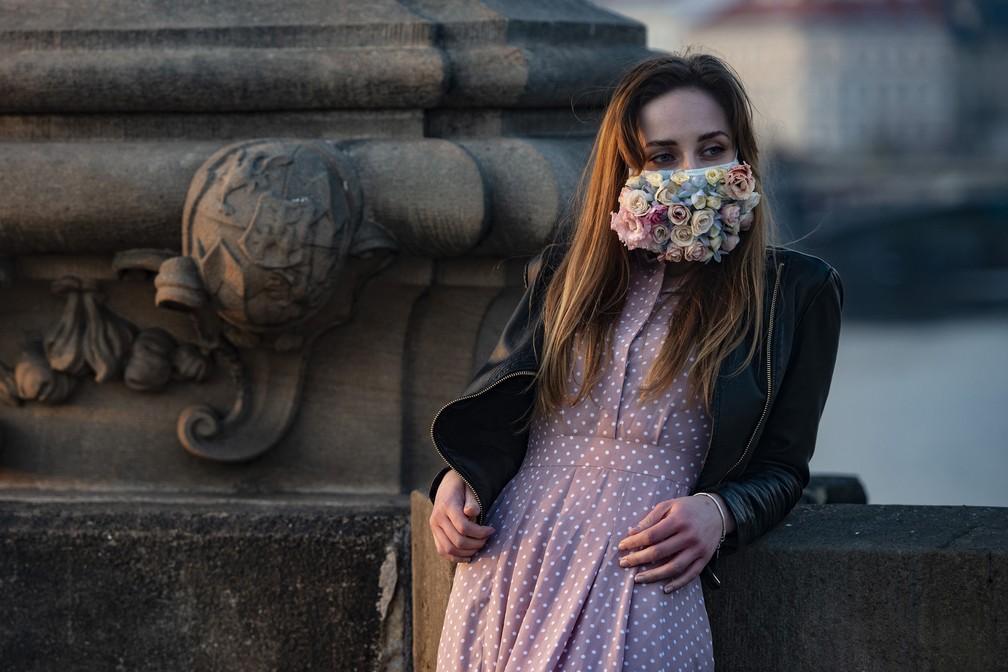 Uma mulher usando uma máscara de proteção é vista na Ponte Carlos, em Praga, onde a maioria das atividades desacelerou ou parou devido à disseminação do novo coronavírus  — Foto: Michal Cizek/AFP