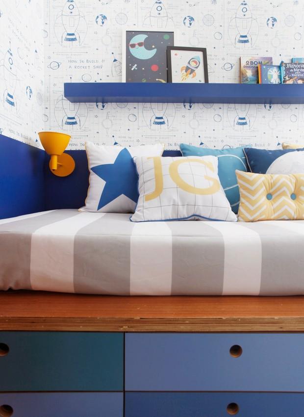A luminária amarela, logo acima da cama, permite a leitura antes de dormir. A prateleira estreita acomoda livros e quadrinhos (Foto: Divulgação)