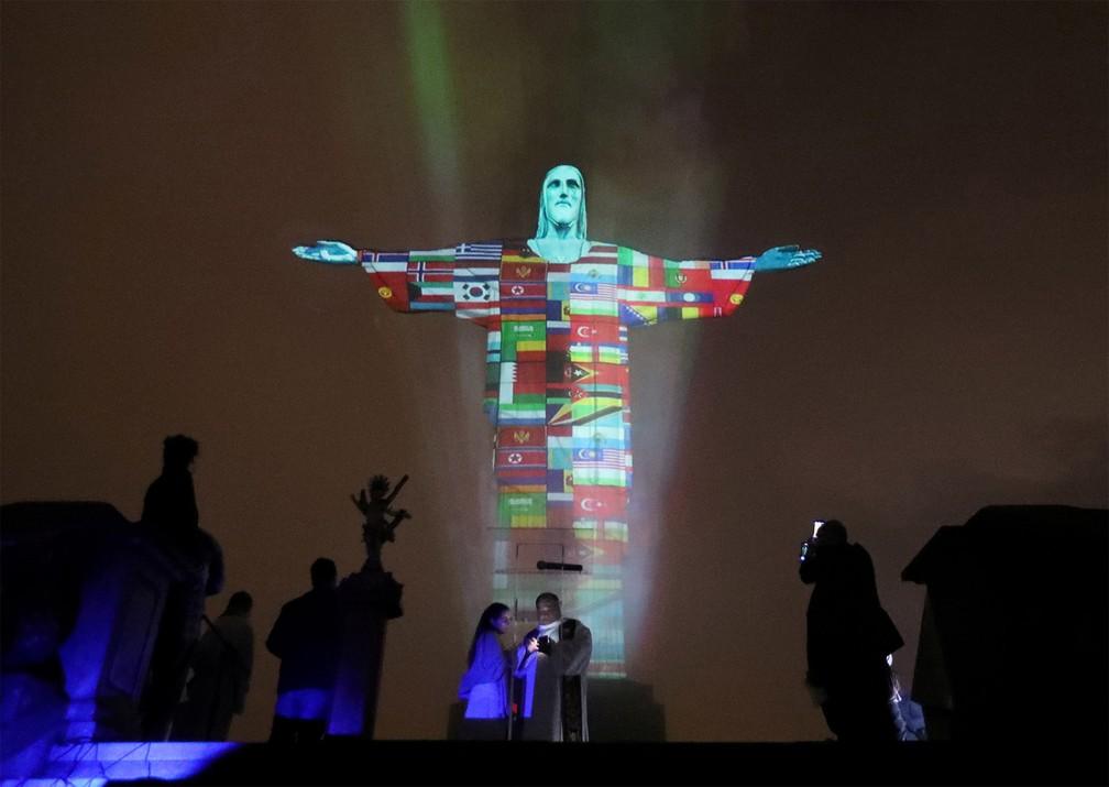 18 de março - No Rio de Janeiro, o Cristo Redentor é iluminado com projeção das bandeiras de países atingidos pelo coronavírus — Foto: Sergio Moraes/AFP