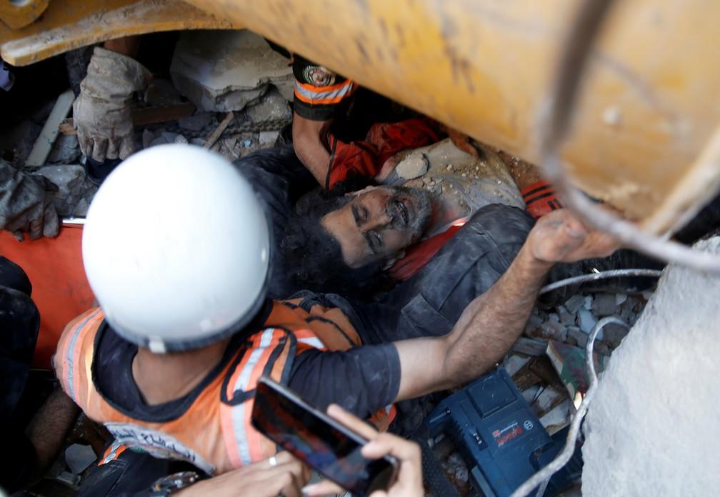 Equipes de resgate atendem uma vítima em meio a escombros no local de ataques aéreos israelenses na cidade de Gaza neste domingo (16)   — Foto: Mohammed Salem/Reuters