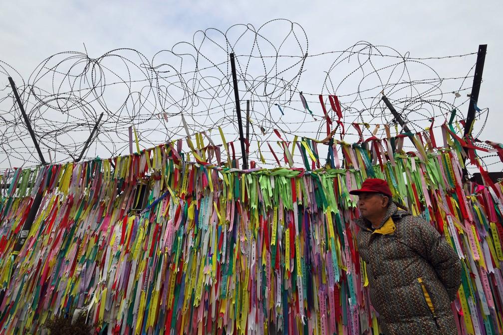 8 de janeiro - Um homem caminha ao lado de uma cerca militar com fitas pedindo por paz e pela reunificação no parque da paz Imjingak, perto da zona desmilitarizada que divide as duas Coreias na cidade fronteiriça de Paju. Na semana passada, os dois países concordaram em ter um diálogo oficial, que não acontecia há mais de dois anos (Foto: Jung Yeon-Je/AFP)