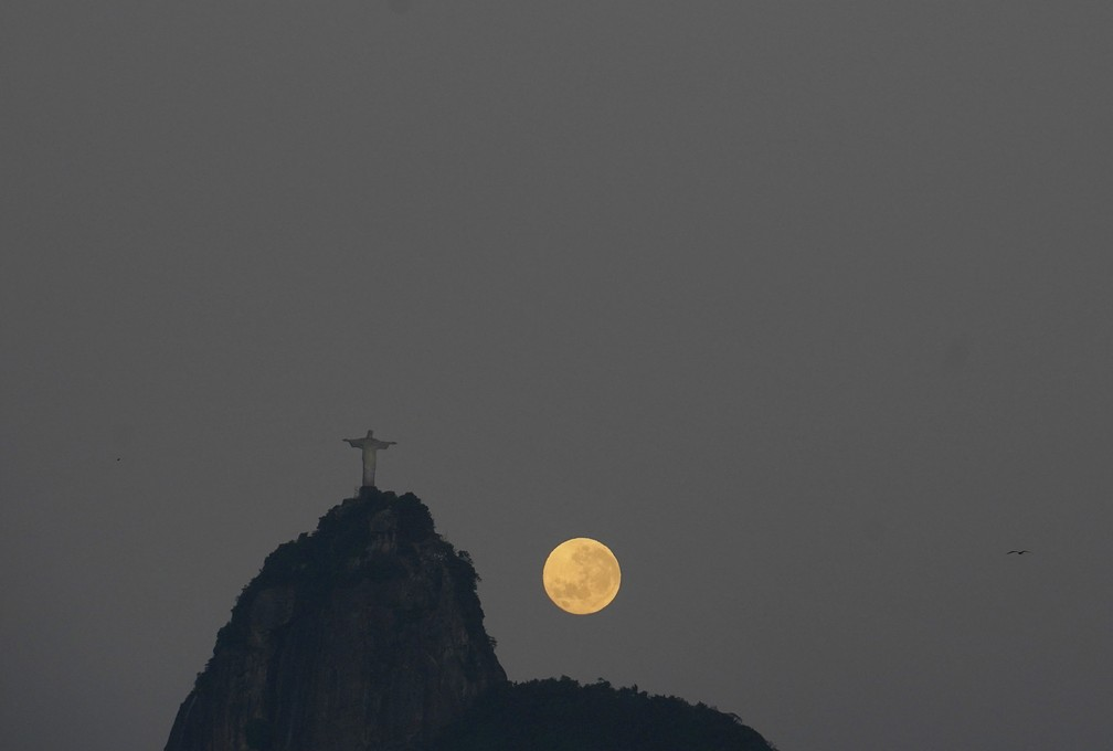 A lua se pondo ao lado do Cristo Redentor na manhã desta sexta-feira (2) — Foto: Marcos Serra Lima/G1
