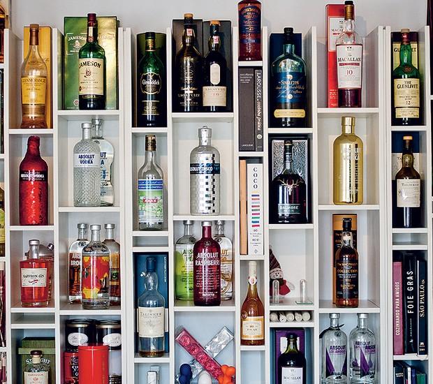 Uma estante com nichos de diversos tamanhos, inspirada em uma biblioteca de Nova York, guarda a coleção de bebidas do empresário Geraldo Mattar, apaixonado por gastronomia. As garrafas ficam ao lado de livros de receitas (Foto: Viviane Gonçalves/Casa e Comida)