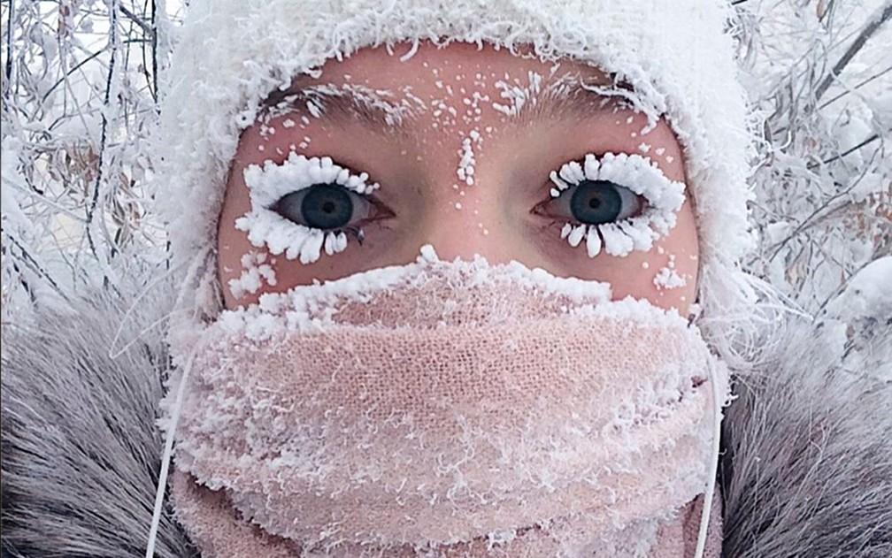 Anastasia Gruzdeva mostra os cílios congelados pelo frio de 50 graus negativos na região de Yakutia, na Rússia, em foto de domingo (14) (Foto: sakhalife.ru photo via AP)