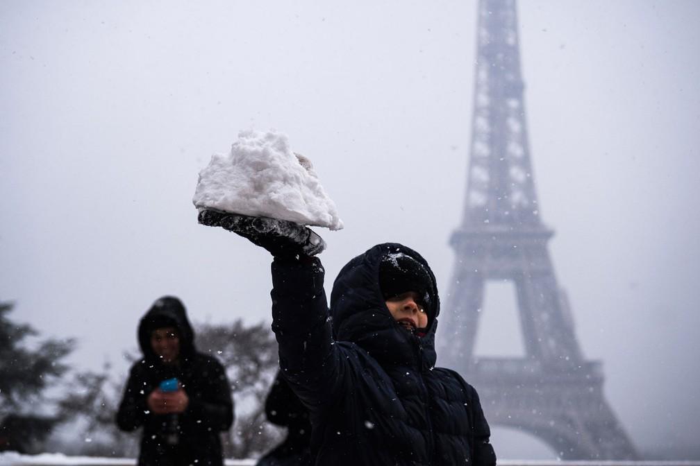 Turista brinca com neve diante de Torre Eiffel nesta terça-feira (6) (Foto: Lionel Bonaventure/AFP)