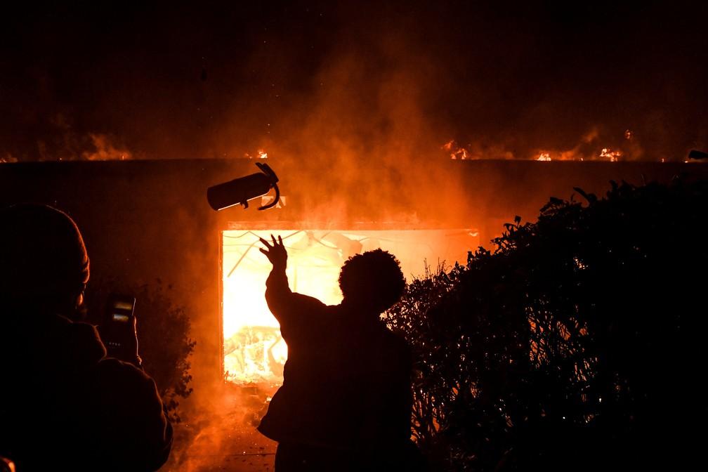 Manifestante joga extintor de incêndio em prédio em chamas durante protesto pela morte de George Floyd em Minneapolis, Minnesota. — Foto: Chandan Khanna / AFP