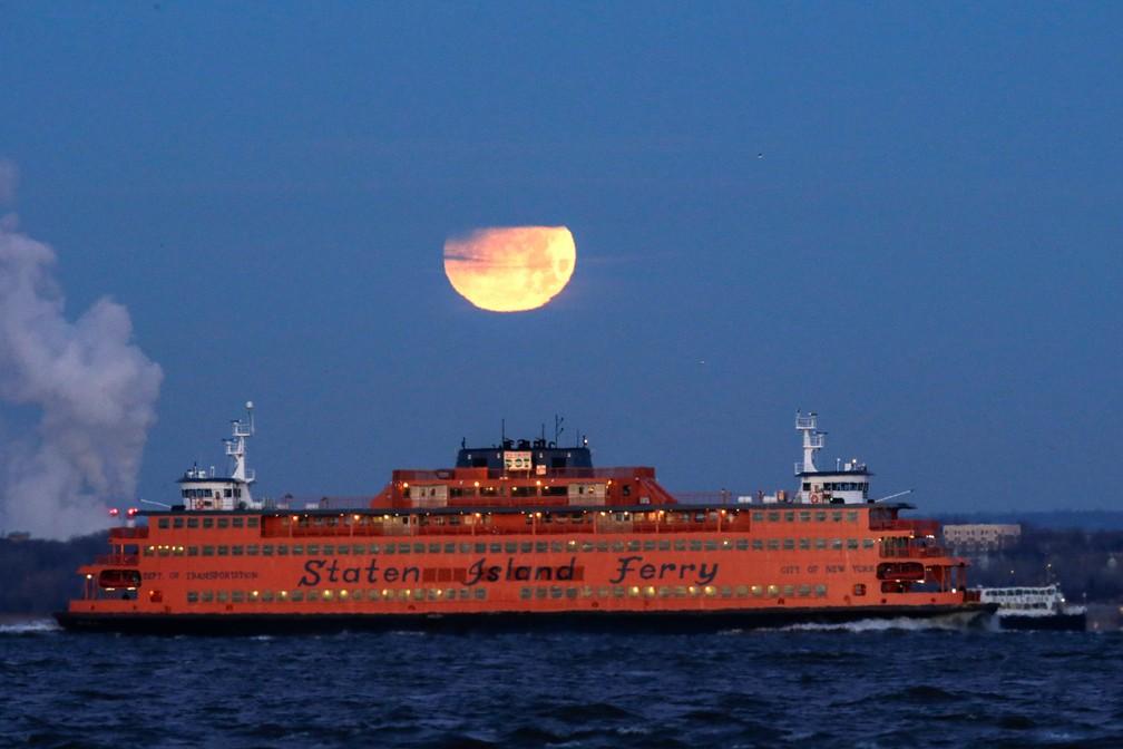 'Superlua azul de sangue', que aconteceu em janeiro deste ano é vista parcialmente eclipsada sobre a balsa de Staten Island vista do Brooklyn, em Nova York, nos EUA (Foto: Eduardo Muñoz/Reuters)