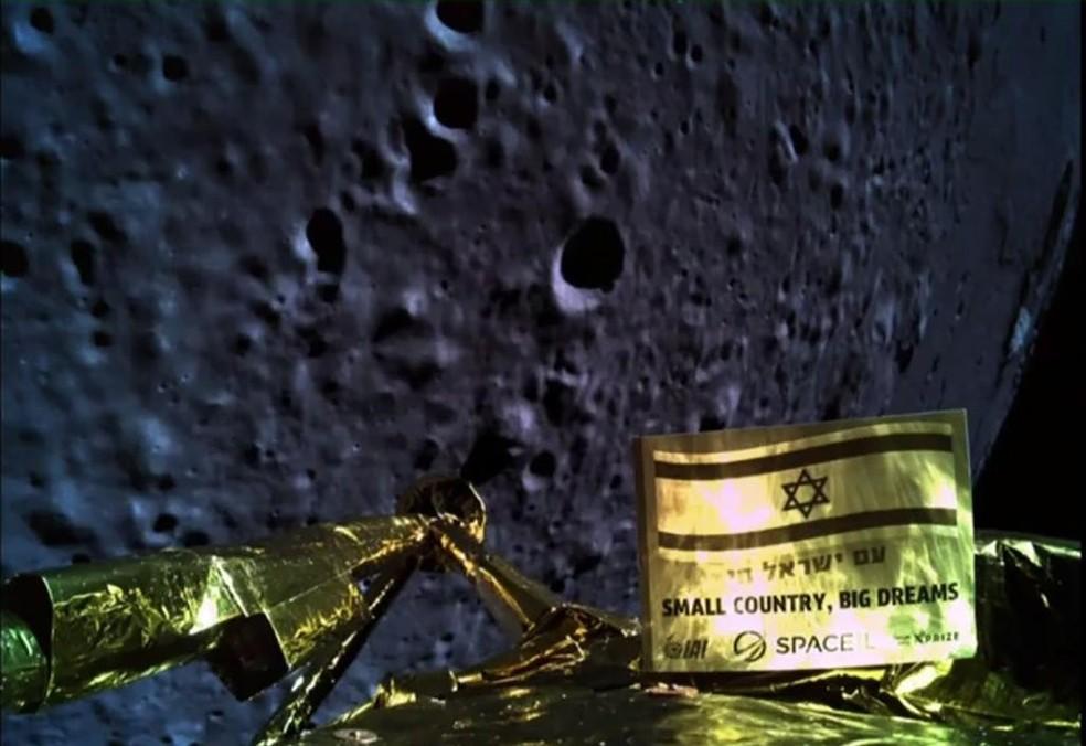 A selfie da nave Beresheet foi tirada a cerca de 13 quilômetros da superfície da lua. Na bandeira israelense os dizeres 'País pequeno, sonhos grandes'. — Foto: Divulgação/SpaceIL e Israel Aerospace Industries