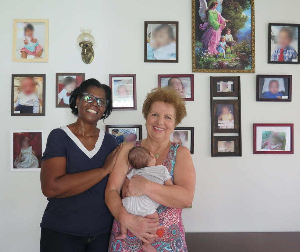 A aposentada tem uma parede reservada para pendurar as fotografias dos bebês que ela já acolheu — Foto: Liliane Souza/G1 Santos