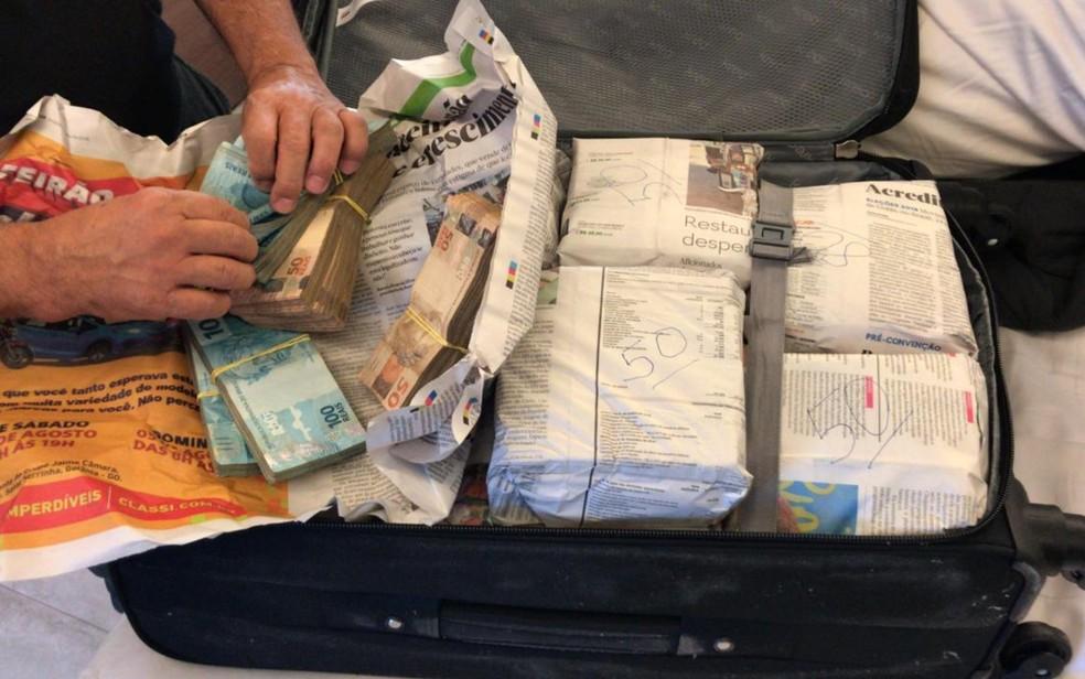 Policiais encontram dinheiro embrulhado em jornal, dentro de mala, em casa de mulher presa durante operação em Goiás, Goiânia — Foto: TV Anhanguera/ Reprodução