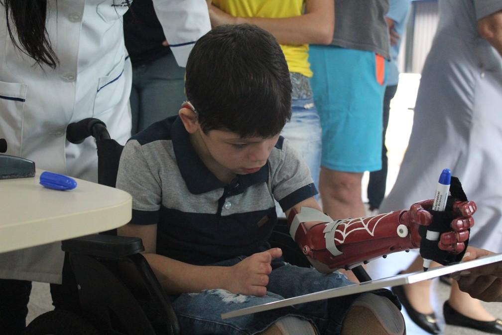 João Victor é destro, mas conseguiu escrever o próprio nome usando a nova mão esquerda.  — Foto: Pedro Bentes/G1