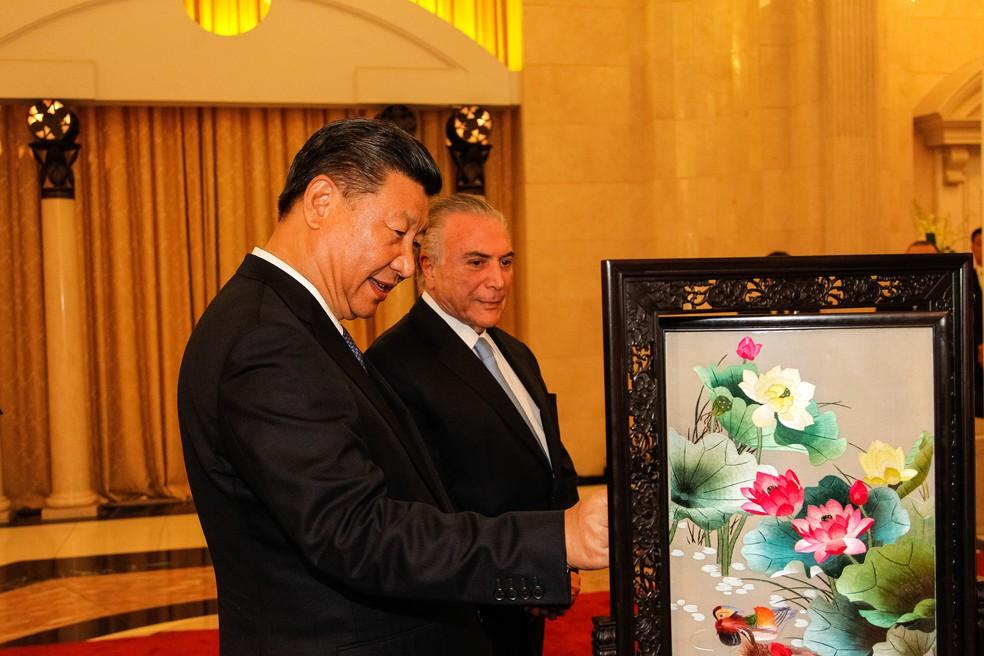 O presidente da China, Xi Jiping presenteia Michel Temer com um quadro após receber uma camisa da Seleção autografada por Pelé (Foto: Beto Barata/PR)