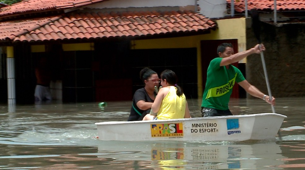 Moradores de Parnaíba usam canoas para se deslocar pelas ruas alagadas após fortes chuvas no litoral do Piauí — Foto: TV Clube
