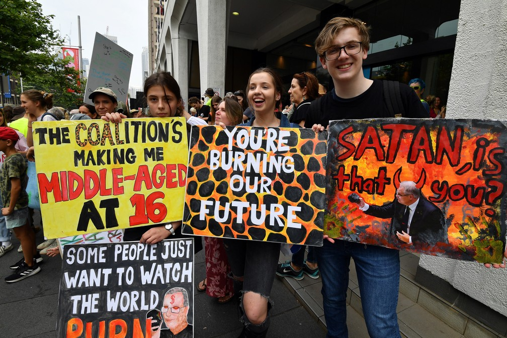 Estudantes australianos seguram cartazes durante manifestação pedindo ação contra as mudanças climáticas em frente à sede na sexta (29) em Sydney  — Foto: Saeed Khan/AFP