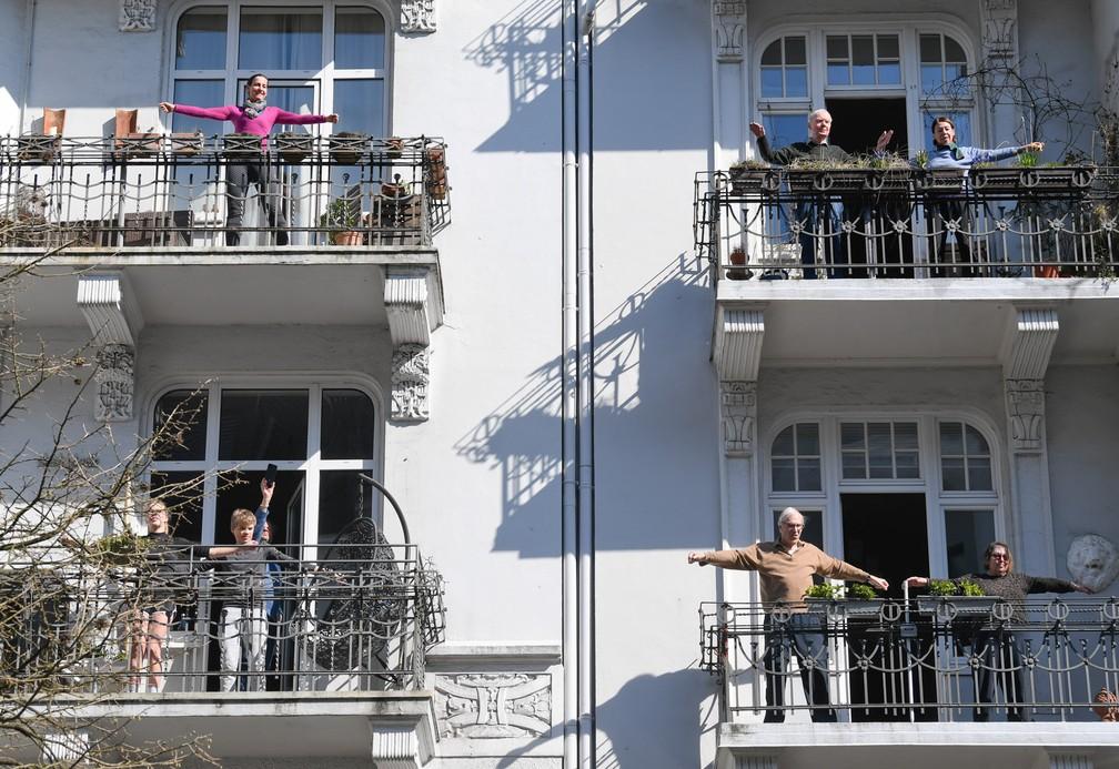 Moradores se exercitam em suas varandas durante o isolamento para evitar a propagação da doença por coronavírus (COVID-19) em Hamburgo, na Alemanha, em 26 de março — Foto: Fabian Bimmer/Reuters