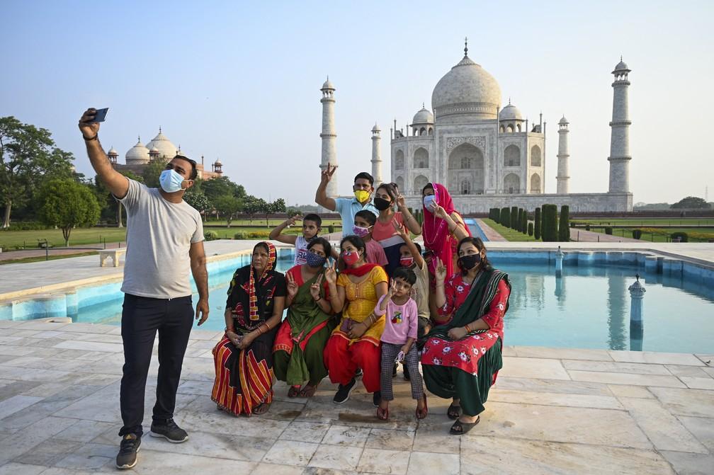 Grupo de turistas tira fotos no Taj Mahal, no dia da sua reabertura aos visitantes, após autoridades reduzirem restrições para combater a Covid-19 em Agra, na Índia, em 16 de junho de 2021 — Foto: Money Sharma/AFP