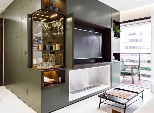 Um louceiro, um bar, um rack para a TV, uma estante e, ainda, uma lareira elétrica! O módulo projetado pelo Mestisso Arquitetura reúne quase tudo no living do apartamento de 80 m² (Foto: Ricardo Bassetti / Divulgação)
