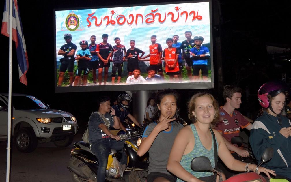 """Motoristas passam por cartaz com foto dos integrantes do time Wild Boar e seu técnico com a mensagem """"bem-vindos irmãos"""", em Chiang Rai, após o resgate do grupo na caverna Tham Luang, na terça-feira (10) (Foto: Tang Chhin Sothy/AFP)"""