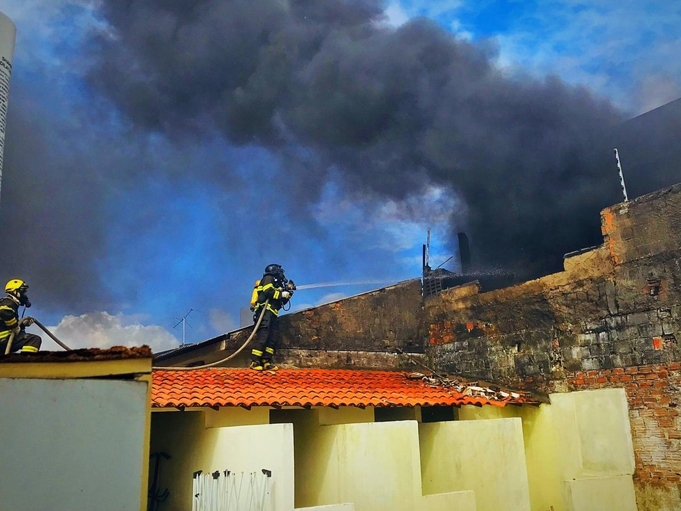 Bombeiro em cima de telhado de casa tentando apagar as chamas em imóvel no Inocop, em Maceió — Foto: Viviane Leão/TV Gazeta