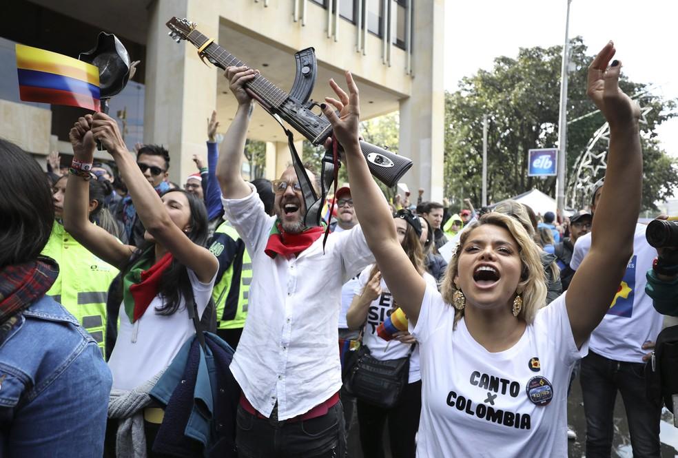O músico colombiano César López, erguendo a 'escopetarra', uma guitarra que incorpora um rifle de assalto como um símbolo de paz, e a cantora Adriana Lucia, participam de um protesto musical contra o governo do presidente Ivan Duque em Bogotá, na Colômbia, neste domingo (8) — Foto: Fernando Vergara/AP