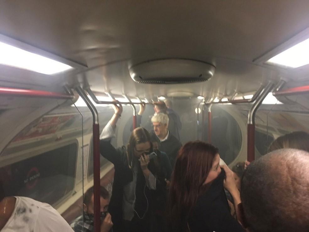 Passageiros tentam se proteger da fumaça em trem da linha Bakerloo, perto de Oxford Circus em Londres, na sexta-feira (11) (Foto:  Joe Bunting/ AP)