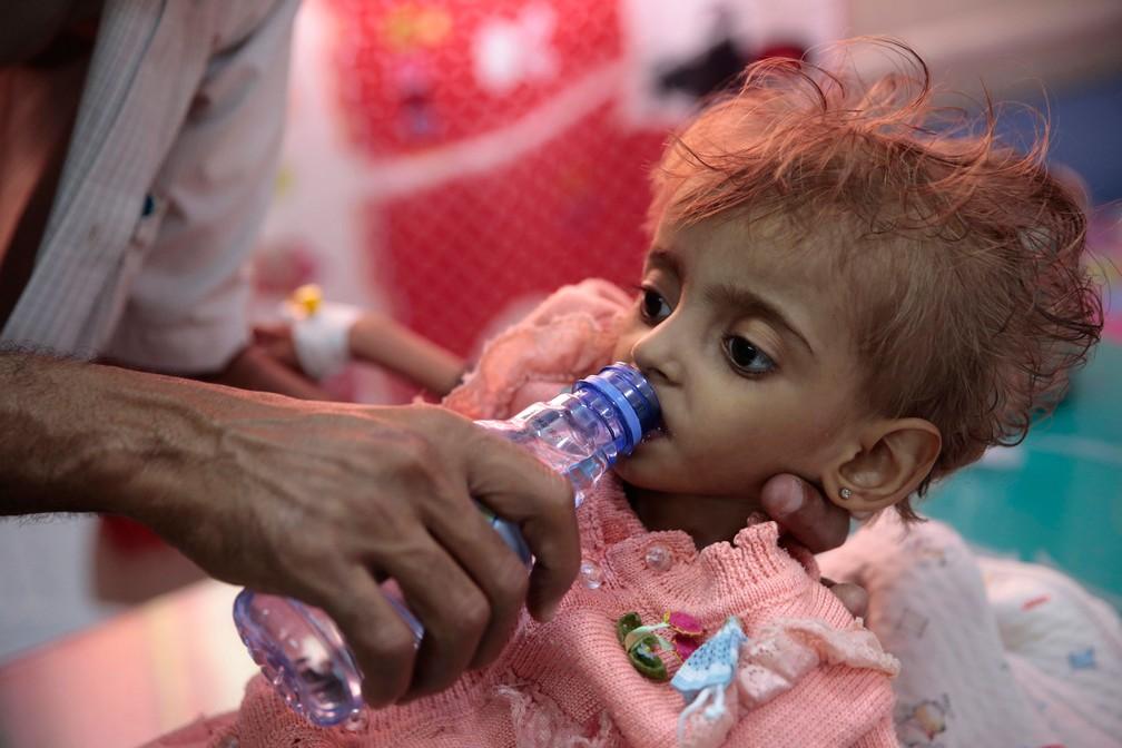 Pai dá água para filha desnutrida em um centro de alimentação em um hospital em Hodeida, no Iêmen, em 27 de setembro  — Foto: Hani Mohammed/AP