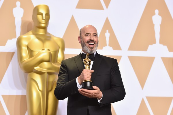 O designer Mark Bridges com o Oscar vencido por ele (Foto: Getty Images)