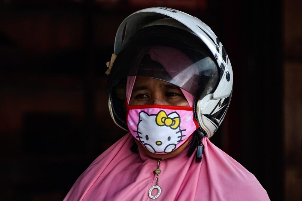 Uma mulher usa uma máscara facial devido à epidemia do novo coronavírus em um mercado de rua em Banda Achém, na Indonésia — Foto: Chaideer Mahyuddin/AFP